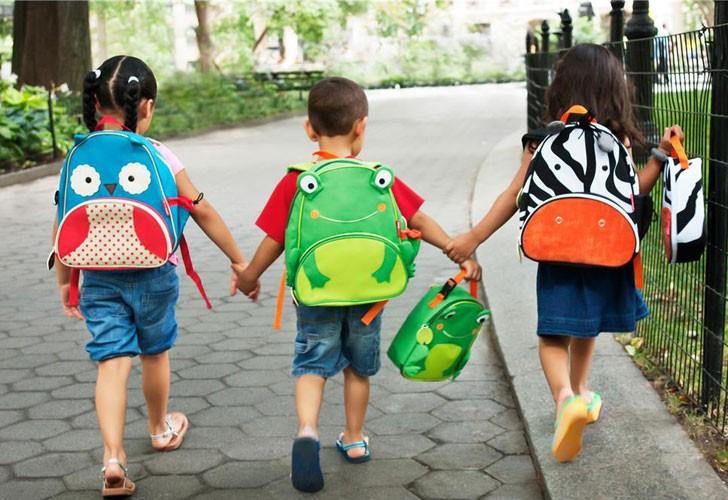 τρια παιδιά νηπιαγωγείου περπατάνε στον δρόμο