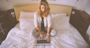 γυναίκα με λάπτοπ στο κρεβάτι